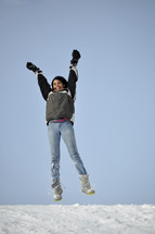 teen girl jumping up in the snow
