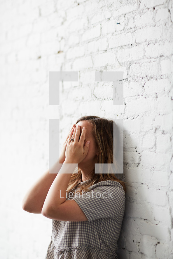a crying woman covering her face