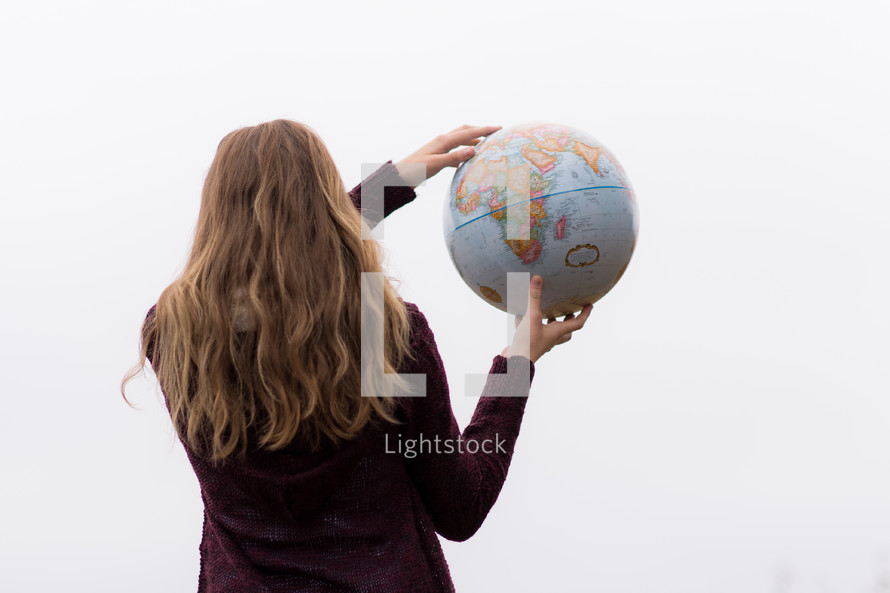 a woman holding a globe