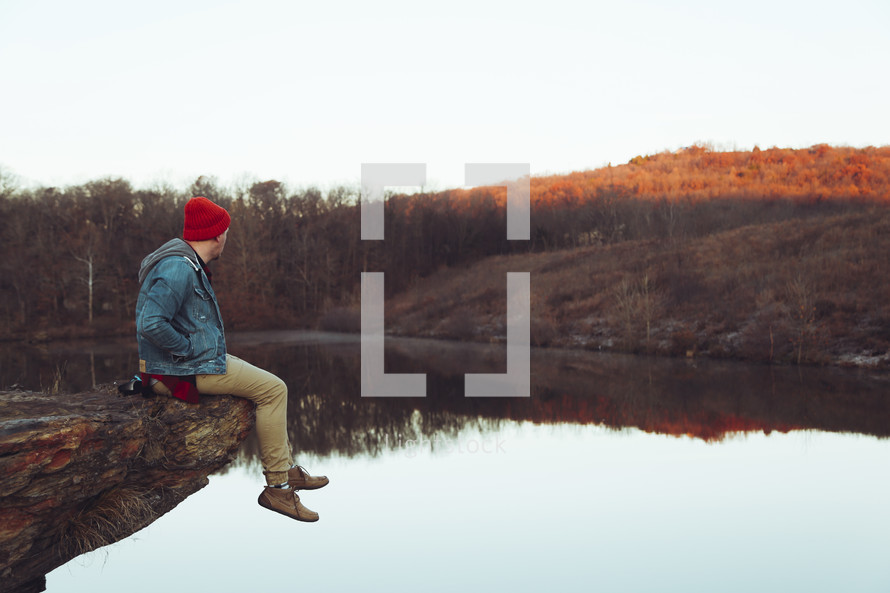 a man sitting on a rock over a lake
