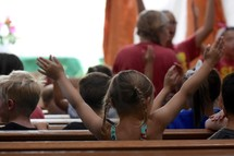 enthusiastic children with raised hands singing worship songs at VBS