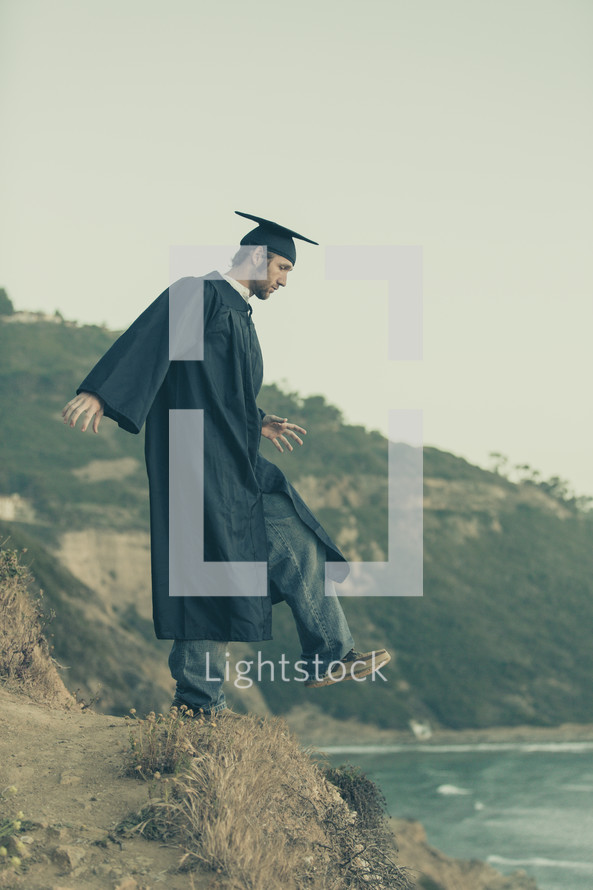 graduate stepping off a cliff