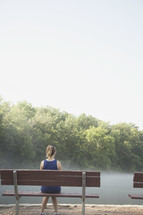 Woman sitting on a park bench in the morning mist.