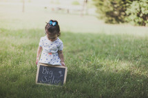 "Girl standing outside in the grass holding a ""big sister"" chalkboard sign."