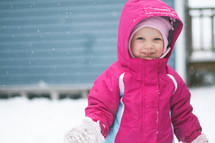 a toddler girl playing in the snow