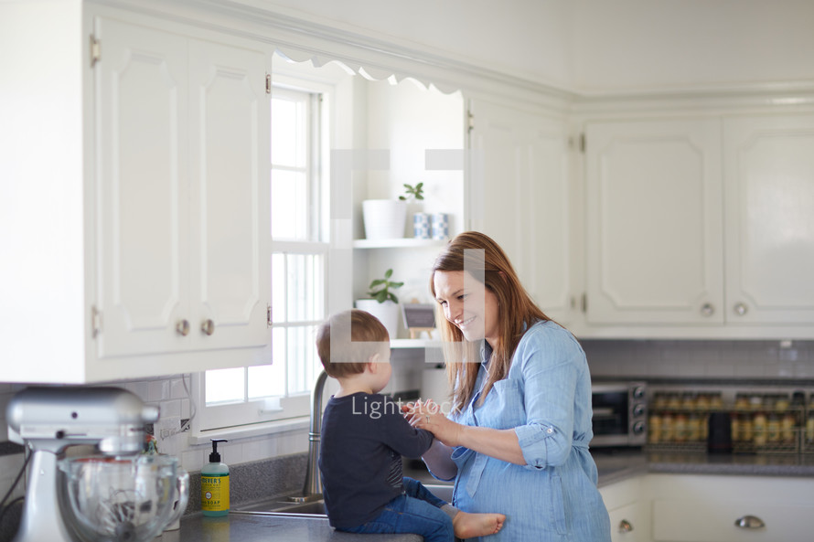 a mother with her toddler son in the kitchen