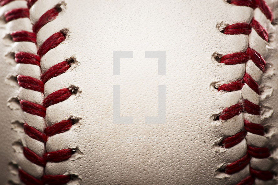 closeup of a baseball with red seams.