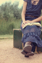 woman sitting on luggage on a dirt road reading a Bible