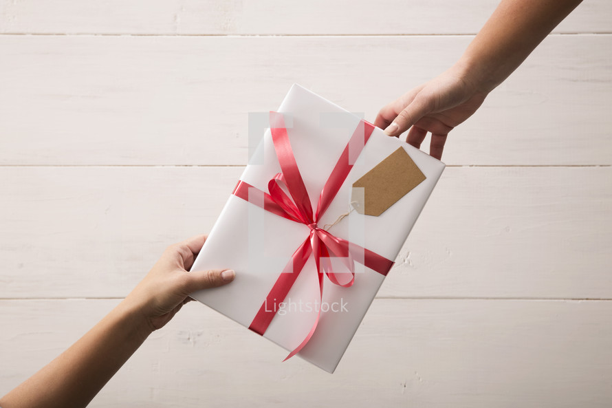 One person giving a gift to another.