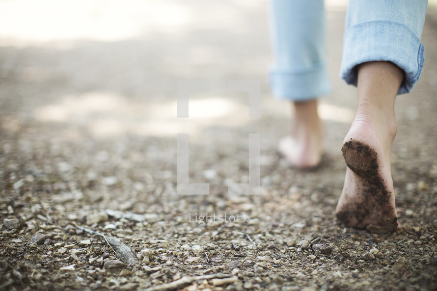 girl walking with bare feet on a trail.