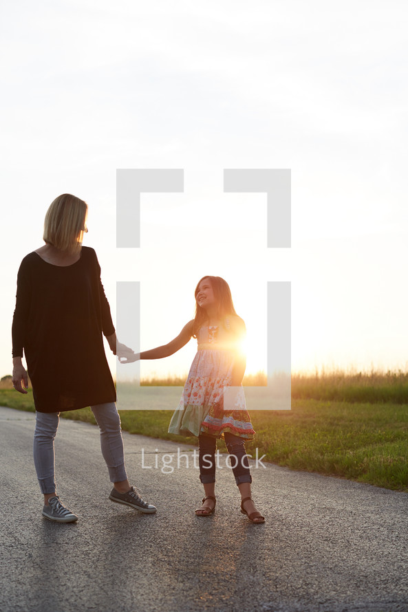 a mother and daughter standing together outdoors at sunset