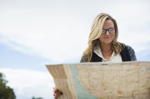 A young woman looking at a road map.