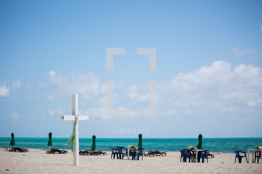 white cross on a beach and lounge chairs