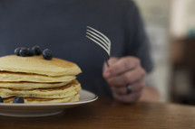 man getting ready to eat pancakes.
