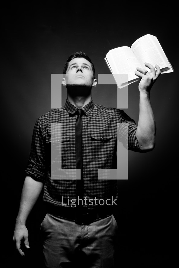 man holding up a Bible while looking to God