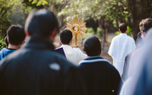 Priest and a crowd walking during a Catholic Eucharistic procession with a monstrance.
