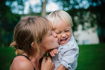 a mother kissing her laughing toddler