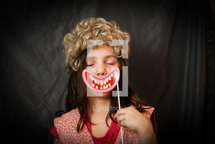 child holding up a silly face mask