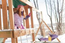 children on a backyard swing set in winter