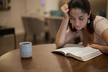 A young woman sitting at a table reading the Bible looking tired