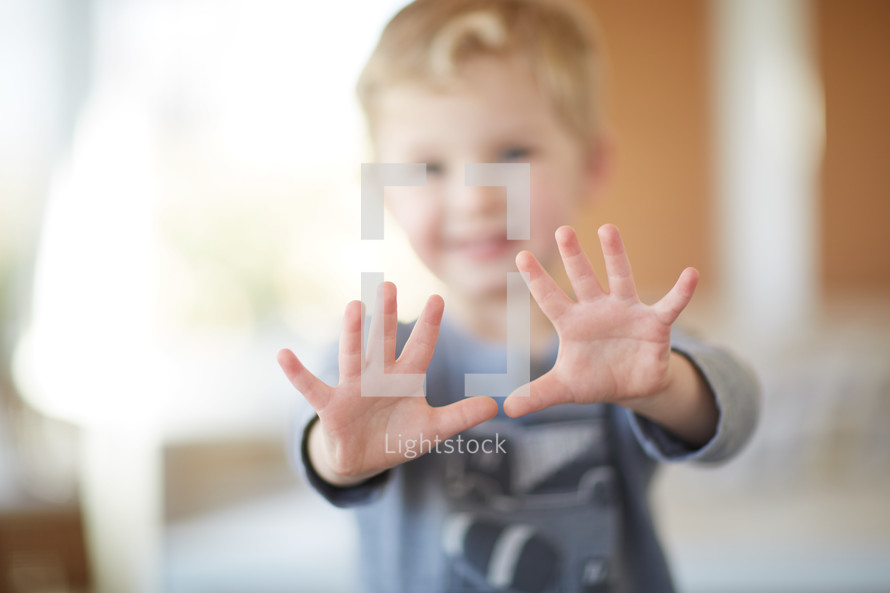 toddler boy holding up both hands