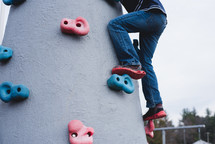 a child on a rock climbing platform on a playground
