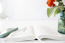 A cell phone and ear phones on an open Bible next to a jar of flowers.