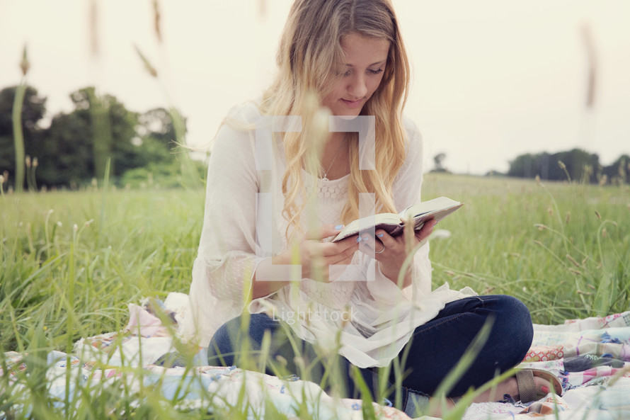 woman sitting on a blanket in the grass reading a Bible