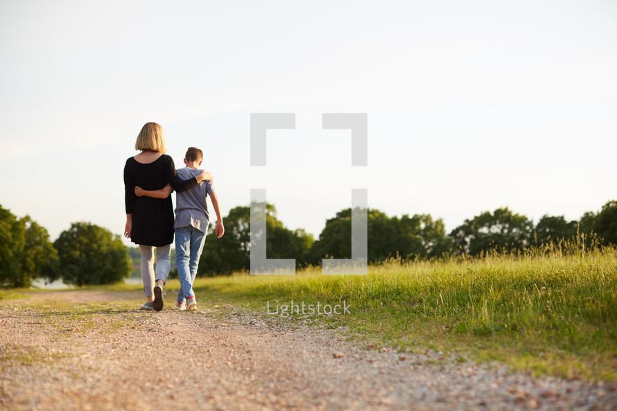 a mother walking with her son on a dirt road