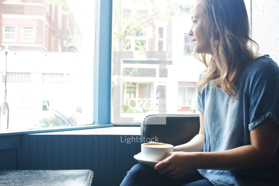 a woman with a coffee cup looking out a window
