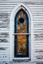 stained glass window on an old rural white church