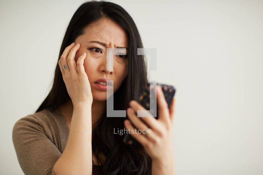 a woman reacting to something on her cellphone screen