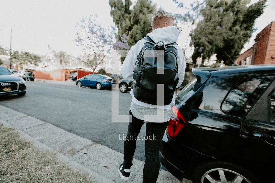 a boy walking down a street with a backpack