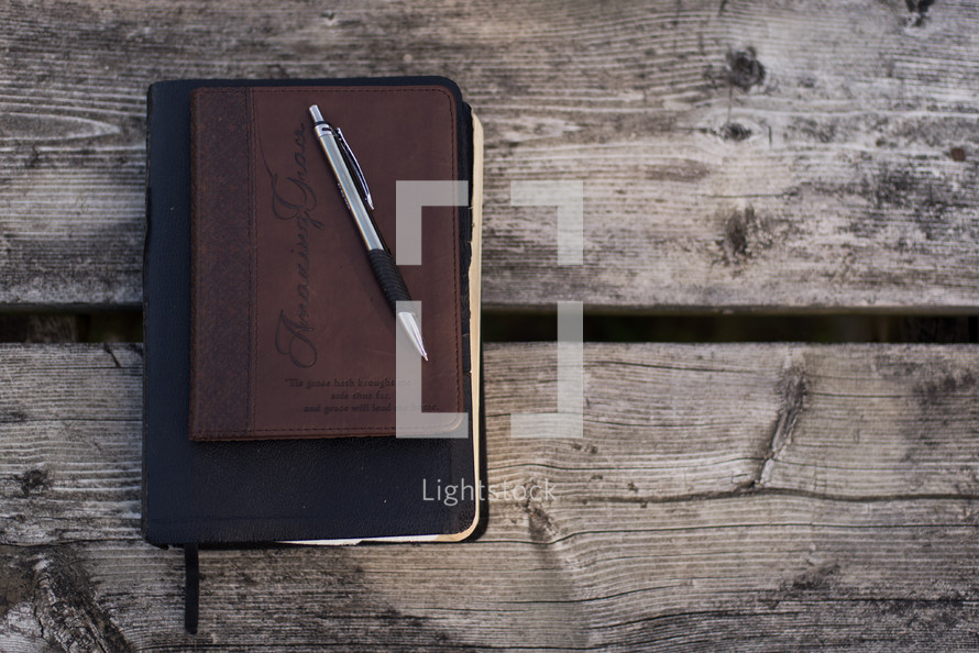 pen on a journal and Bible