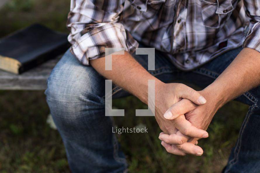 a man praying at a picnic table