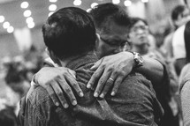 men hugging at a worship service