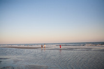 boys walking on a beach at sunset