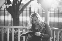 a woman reading a Bible in a gazebo