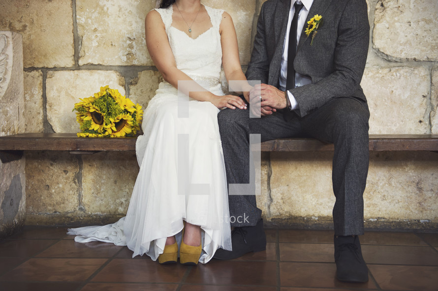 Bride with sunflower bouquet sitting on wooden bench holding hands with groom in chapel.