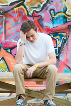 a young man sitting on a bench with his head down and a graffiti covered wall
