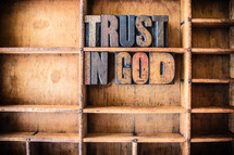 "Wooden letters spelling ""Trust in God"" on a wooden bookshelf."
