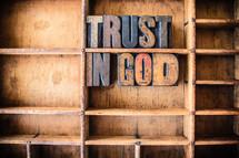 "Wooden letters spelling ""Trust in God"" on a wooden bookshelf."
