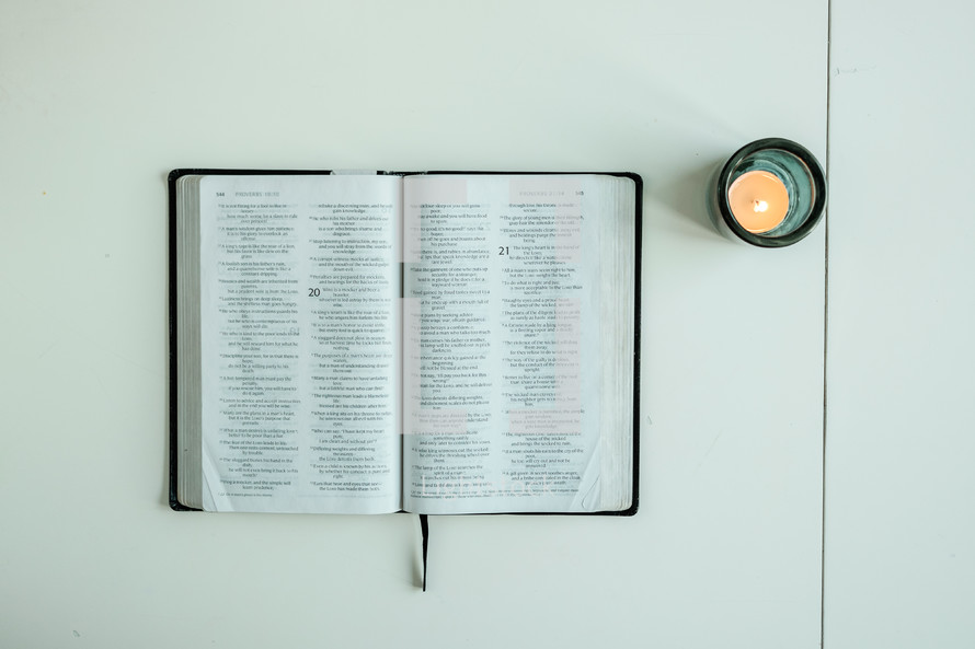 open Bible and votive candle