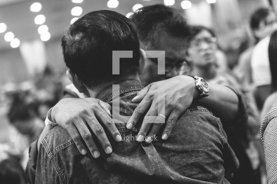 men hugging at a worship service
