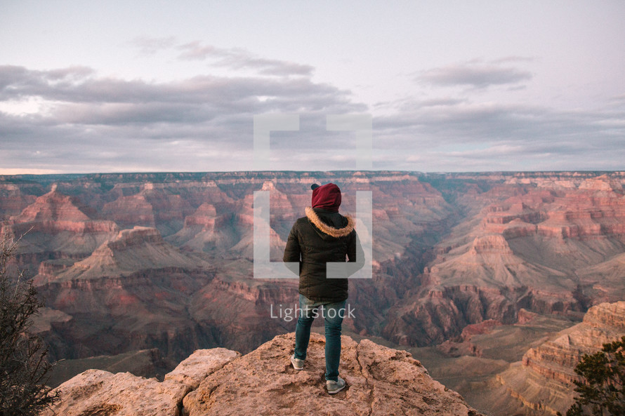 a man standing at the edge of a cliff looking out at canyons