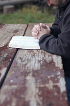 man praying near and open Bible on a picnic table