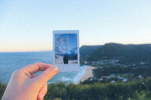 woman holding up a polaroid picture near a coastline