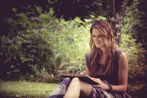 A young woman sitting against a tree and reading a book.