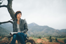 Woman sitting outside, leaning against a tree, reading the Bible.
