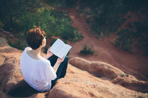 Woman sitting outside on a hilltop reading the Bible.